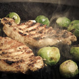 Pork and brussels sprouts on grill pan. Selective focus. Toned Royalty Free Stock Photo