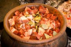 Preparation of food in earthy boiler-pans, pork with vegetable. Pork buns, pork knees, pork shoulder, with cabbage in earthy boiler-pans earthen dish royalty free stock photos