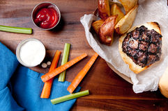 Pork burger with wedge fries take out. Ethically raised pork burger with hand cut red potato wedges and vegetable sticks take out stock photo Stock Images