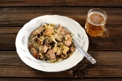 Pork with cabbage and a glass of light beer. On old wood board Stock Images