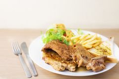 Pork and chicken steak with salad and french fried. On wood table Royalty Free Stock Photo