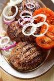 Pork chop. Grilled pork chop with tomato and onion Stock Photos
