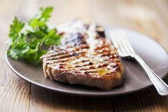 Pork chop. Juicy grilled pork chop (neck cut) with greens stock images