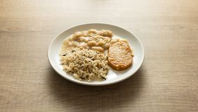 Pork chop, Brown rice and white beans. White dish on wooden tabl Stock Photo