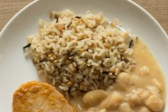 Pork chop, Brown rice and white beans. White dish on wooden tabl Royalty Free Stock Photography