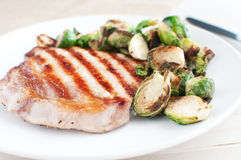 Pork chop with brussels sprouts Royalty Free Stock Images