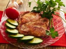 Pork chop. Cucumber tomato parsley garlic Stock Images