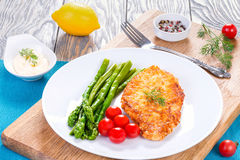 Pork chop fried in tempura on a white plate Stock Photography