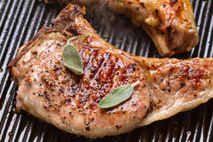 Pork chop in a frying pan grill closeup Stock Photos