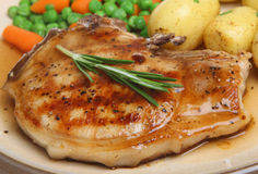 Pork Chop with Gravy. Pan-fried pork chop with new potatoes, vegetables and gravy Royalty Free Stock Photos
