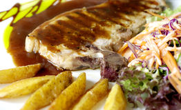Pork chop and gravy with fries and salad Stock Photo