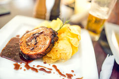 Pork chop on grill with chips as main course at local restaurant, fancy dish from american cuisine Royalty Free Stock Photography