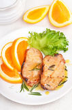 Pork chop with orange sauce. Delicious pork chop with orange sauce on white plate stock images