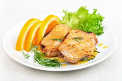 Pork chop with orange sauce. On white plate stock image
