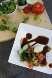 Pork chop,Parsley bowl and vegetables. Parsley and other vegetable ingredients on white plate on patio table in SUmmer close up of parsley Stock Photos