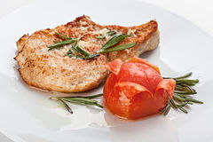 Pork chop on the plate is served with tomato and rosemary. Stock Photos