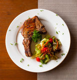 Pork chop with salad on table top view Royalty Free Stock Image