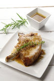 Pork chop with sauce. Delicious pork chops with sauce and herbs royalty free stock photos