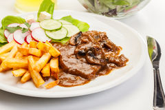 Pork chop with sauce, mushrooms and chips Stock Image