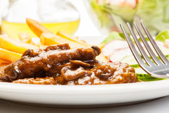 Pork chop with sauce, mushrooms and chips Royalty Free Stock Images