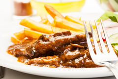 Pork chop with sauce, mushrooms and chips Stock Photography