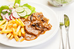 Pork chop with sauce, mushrooms and chips Stock Photos