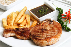 Pork chop served with fries and black pepper sauce Stock Image