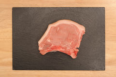 Pork chop on slate Stock Images