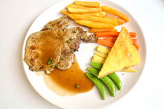 Pork chop steak and gravy on white dish Royalty Free Stock Photo