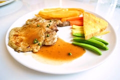 Pork chop steak and gravy on white dish Stock Photography