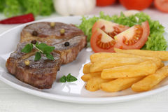 Pork chop steak meat meal with fries, vegetables and lettuce on Royalty Free Stock Photo
