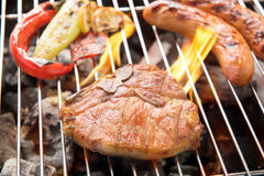 Pork chop steak and vegetable with sausage on a flaming BBQ gril Royalty Free Stock Image