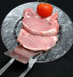 Pork chops. Two center cut pork chops, tomato and tools on a clear plate Royalty Free Stock Photography