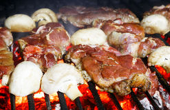 Pork chops and Champignon mushrooms grilling on a BBQ Stock Photos