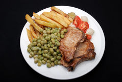 Pork chops chips and peas Stock Photography