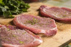 Pork chops on a cutting board with fresh herbs. Close up of pork chops on a cutting board with fresh herbs. Selective focus Royalty Free Stock Images