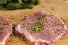 Pork chops on a cutting board with fresh herbs. Selective focus Royalty Free Stock Photos
