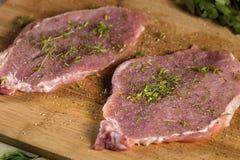Pork chops on a cutting board with herbs. Pork chops on a cutting board with fresh herbs. Selective focus Stock Photos