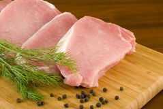 Pork chops with fresh dill on a cutting board Royalty Free Stock Images