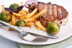 Pork chops with fries and brussels sprouts Royalty Free Stock Photos