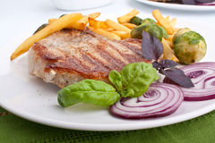 Pork chops with fries and brussels sprouts Stock Photos