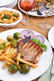 Pork chops with fries, brussels sprouts and wine Stock Photo