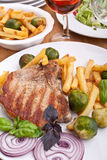 Pork chops with fries, brussels sprouts and wine Stock Images