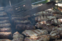 Pork chops and mici on the grill. On the grill, many pork chops and traditional romanian meat balls named mici or mititei. Man attends to the barbeque rotating Royalty Free Stock Photos