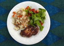 Pork chops, rice and salad on a plate Stock Photos