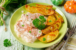 Pork chops with sour cream and baked potatoes Stock Photo