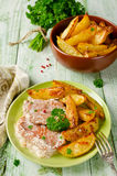 Pork chops with sour cream and baked potatoes Royalty Free Stock Photography