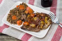 Pork chops with tomatoes on top with lentils and carrots Stock Photo