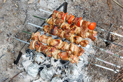 Pork cooked on the grill. Meat cooked on the coals. Pork being prepared fire. Pork kebab. Meat with onions and vegetables. Stock Photo