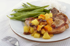 Pork cop with chutney. Pork chop dinner with apple raisin orange chutney and green beans Royalty Free Stock Images